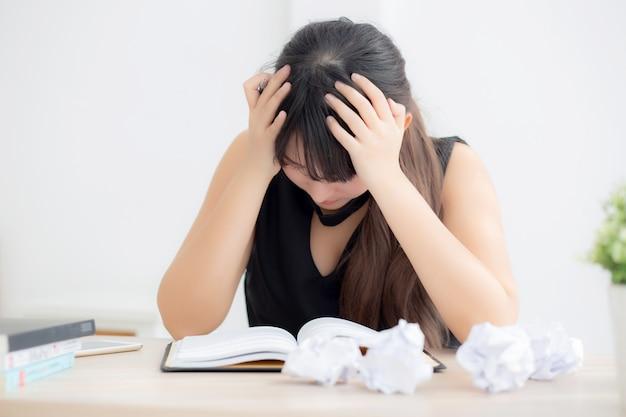 Aziatische vrouw moe en benadrukt met overwerkt schrijven.