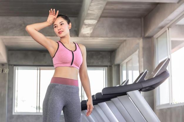 Aziatische vrouw moe na training training bij fitness gym.