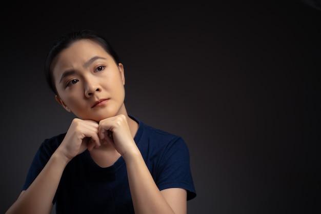 Aziatische vrouw na te denken over probleem, bezorgde en verwarde emotie geïsoleerd op de achtergrond.
