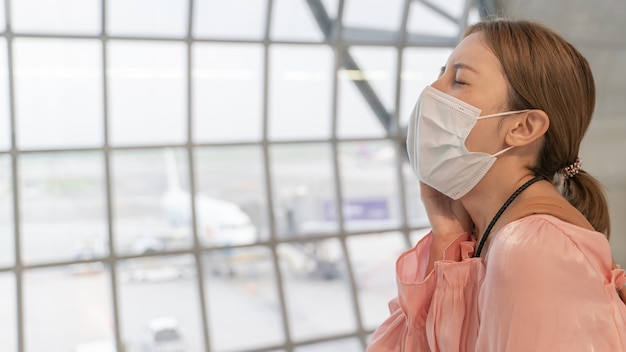 Aziatische vrouw niest terwijl ze maskers draagt op de luchthaventerminal. nieuw normaal, covid19-ziektepreventieconcept.