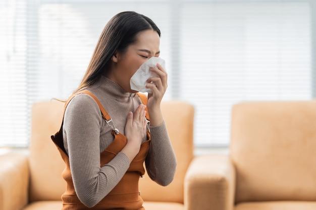 Aziatische vrouw niest. ze gebruikt een tissue om haar mond te bedekken en ze werkt thuis.