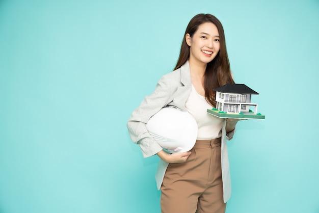 Aziatische vrouw of ingenieur die een wit helm en een huismodel houden dat op groene achtergrond wordt geïsoleerd