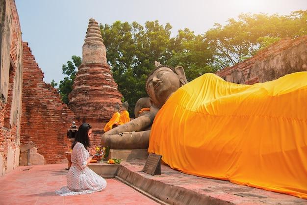 Aziatische vrouw om eerbied te betonen aan boeddhabeeld in ayutthaya, thailand.