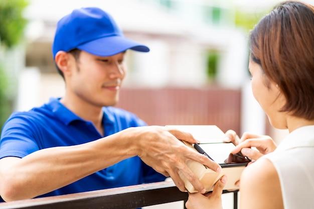 Aziatische vrouw ondertekent elektronische handtekening naar draagbaar mobiel apparaat na ontvangstpakket