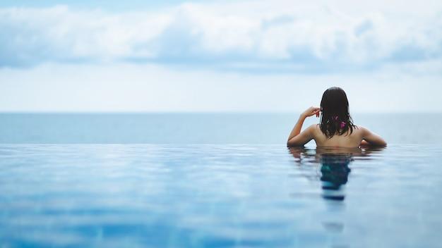 Aziatische vrouw ontspannen in het zwembad op het strand
