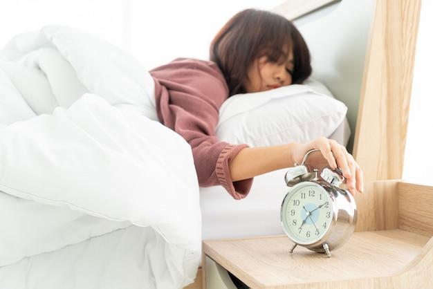 Aziatische vrouw op bed en 's ochtends wakker worden