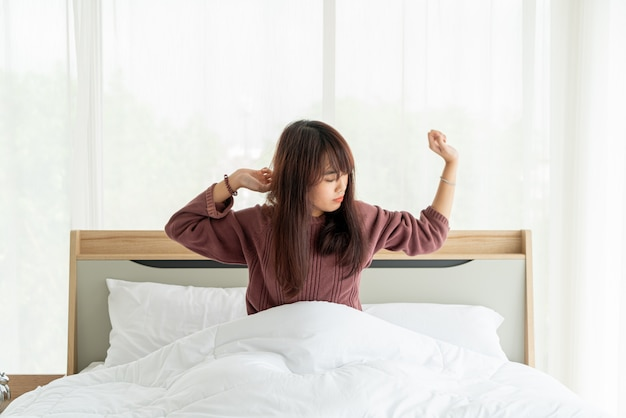 Aziatische vrouw op bed en wakker in de ochtend