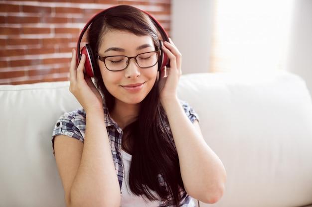 Aziatische vrouw op de laag die aan muziek luistert