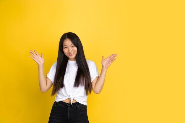 Aziatische vrouw op gele muur, emoties