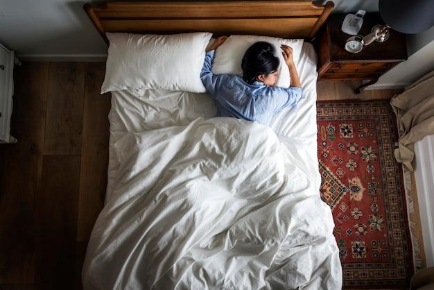 Aziatische vrouw op het bed die alleen slapen