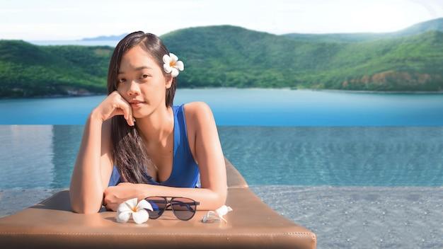 Aziatische vrouw op vakantie naast het zwembad