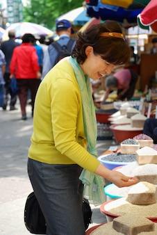 Aziatische vrouw op zoek naar granen in de markt