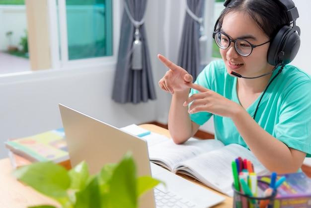 Aziatische vrouw op zoek naar videoconferentie bellen op een laptop computer meisjesstudenten spreken reageren met hoofdtelefoon microfoon klasse universiteit leren internet online afstandsonderwijs vanuit huis