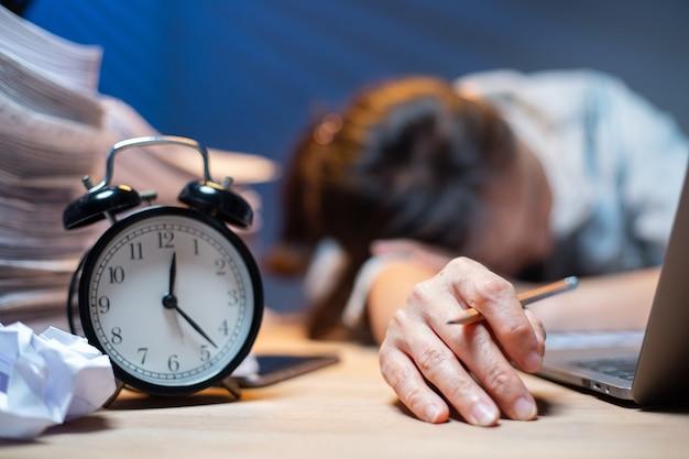 Aziatische vrouw overwerkt en slaapt op de tafel nadat ze zich erg moeilijk voelt. depressie en angst. chinees kantoormeisje dat daarna slaapt, kan geen gegevens en oplossing vinden om haar rapport te doen. workaholic-mensen.