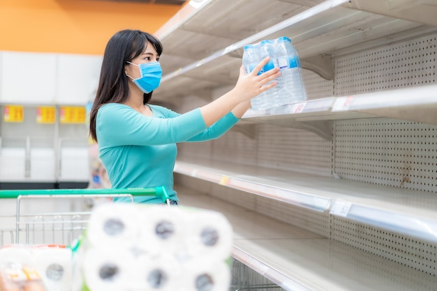 Aziatische vrouw pakt laatste fles waterfles op in de lege schappen van de supermarkt te midden van covid-19 coronavirus angsten, shoppers in paniek bij het kopen en opslaan van toiletpapier ter voorbereiding op een pandemie.