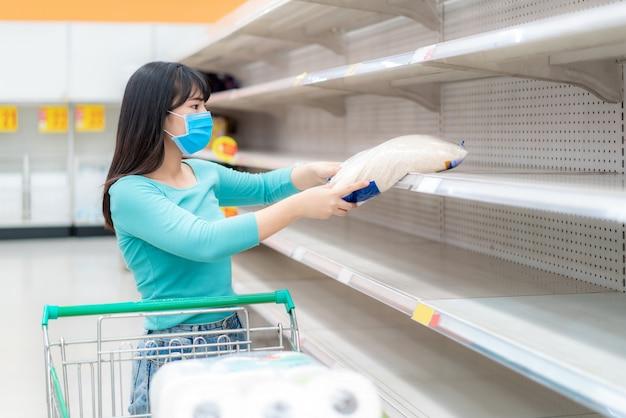 Aziatische vrouw pakt laatste rijstpakket op in lege schappen van supermarkt te midden van covid-19 coronavirus angsten, shoppers in paniek bij het kopen en opslaan van toiletpapier als voorbereiding op een pandemie.