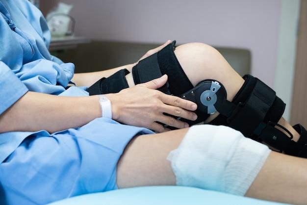 Aziatische vrouw patiënt met verband compressie kniebrace ondersteuning letsel op het bed in het ziekenhuis verpleging. gezondheidszorg en medische ondersteuning.