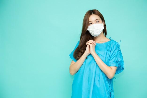 Aziatische vrouw patiënt pak dragen wit gezichtsmasker geïsoleerd op groene studio achtergrond