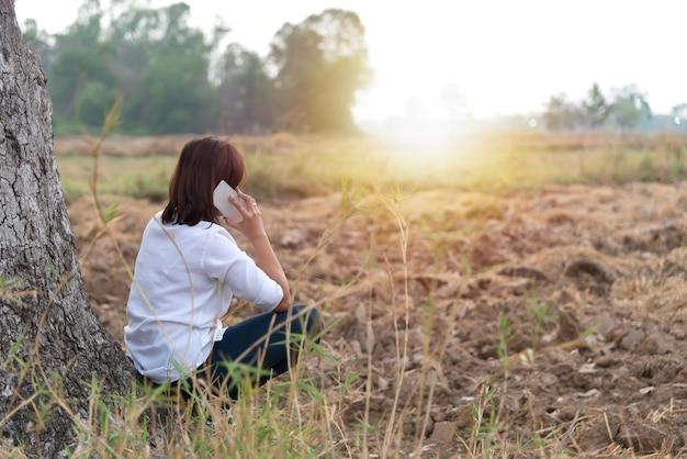 Aziatische vrouw praat telefoon in het veld met fel zonlicht, land meisje