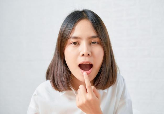 Aziatische vrouw prachtige charmante raakt haar mond met haar hand.