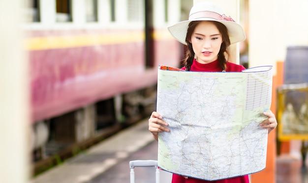 Aziatische vrouw pregnan in rode kleding die rode bagage draagt en de kaart bekijkt