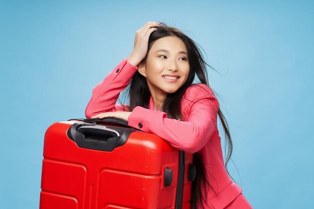 Aziatische vrouw reist met een koffer in haar handen, vakantie