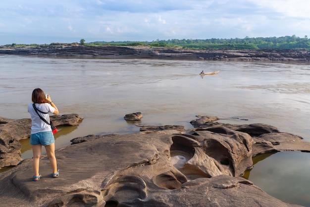 Aziatische vrouw reizen gebruik smartphone foto van rivier en boot in sam pan bok rotslandschap