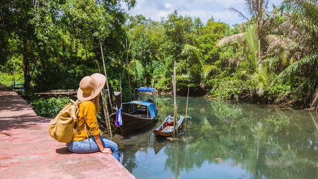 Aziatische vrouw reizen natuur. reis ontspannen. een bootfoto. zittend kijken naar de prachtige natuur bij tha pom-klong-song-nam. krabi, in thailand.