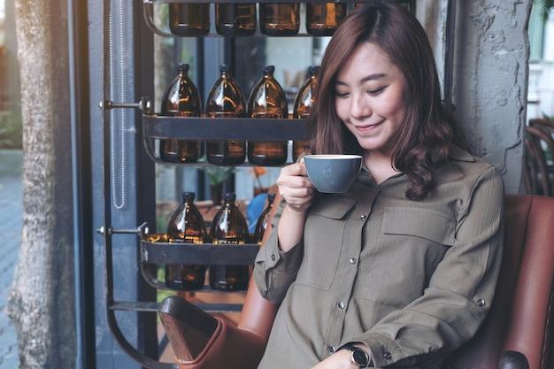 Aziatische vrouw ruiken en warme koffie drinken met een goed gevoel in café