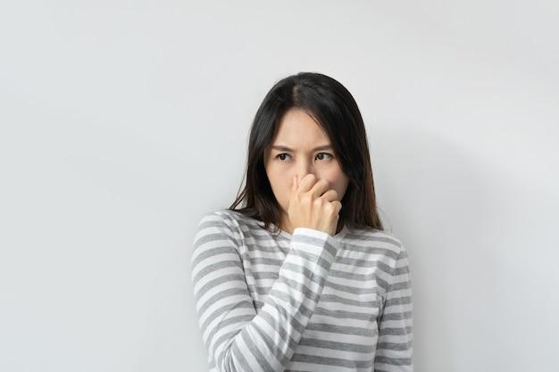 Aziatische vrouw ruikt iets stinkends en walgelijks, ondraaglijke geur, adem inhoudend met vingers op de neus. meisje knijpt neus met vingers kijkt met walging iets stinkt slechte geur. ruimte kopiëren