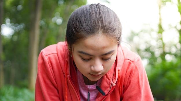 Aziatische vrouw rust na het hardlopen. dragen jas en oortelefoon