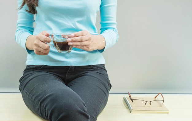 Aziatische vrouw rust voor koffie drinken in haar vrije tijd op houten bureau