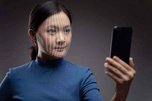 Aziatische vrouw scant gezicht door slimme telefoon met behulp van gezichtsherkenningssysteem. geïsoleerd