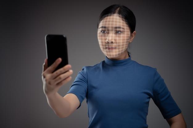 Aziatische vrouw scant gezicht door slimme telefoon met behulp van gezichtsherkenningssysteem