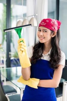 Aziatische vrouw schoonmaak ramen in haar huis genieten van het karwei