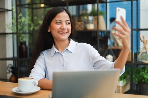 Aziatische vrouw selfie met mobiele telefoon in de koffieglimlach van de koffiewinkel en gelukkig gezicht