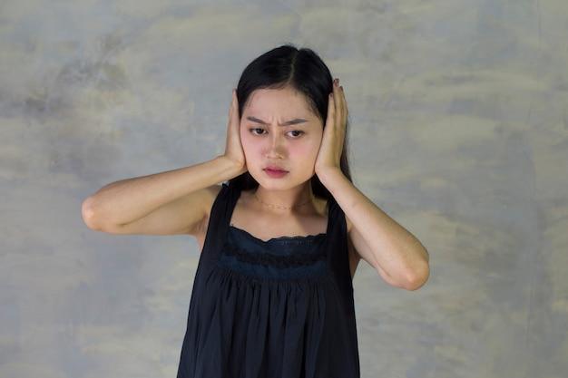 Aziatische vrouw sluit haar oren met handen die weigeren om naar iets te luisteren,