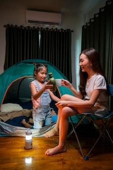 Aziatische vrouw speelt en verblijft in tent met haar dochter en heeft plezier met campingtent in hun slaapkamer
