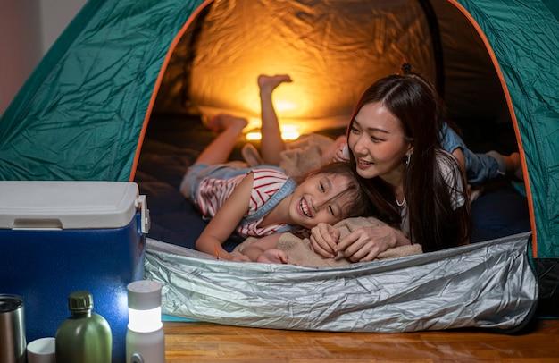 Aziatische vrouw speelt en verblijft in tent met haar dochter en heeft plezier met kampeertent in hun slaapkamer een staycation-levensstijl een nieuw normaal voor sociale afstand nemen bij een uitbraak van het coronavirus
