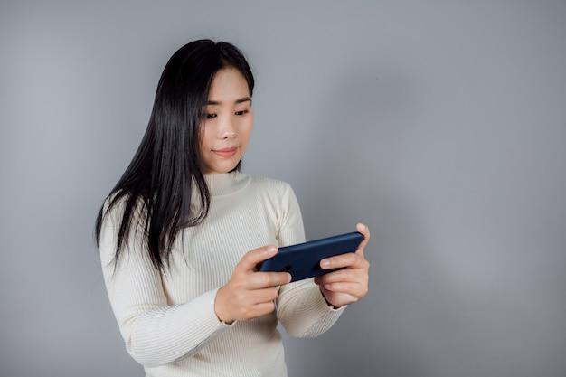 Aziatische vrouw spelen op tablet slimme telefoon tegen op grijze achtergrond