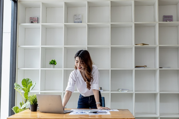 Aziatische vrouw staat aan haar bureau in haar kantoor, ze is een kantoormedewerker als hoofd van de marketingafdeling, ze bekijkt documenten om het marketingplan te analyseren om de verkoop te verhogen. kantoor werk concept.