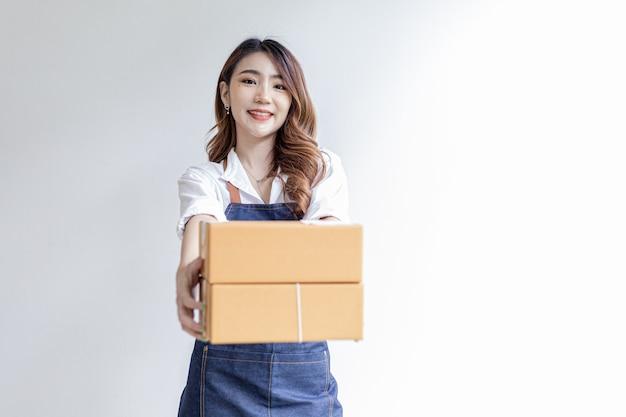 Aziatische vrouw staat met pakketdozen, ze heeft een online winkel, ze verpakt en verzendt via een particulier transportbedrijf. online verkoop en online winkelconcepten.