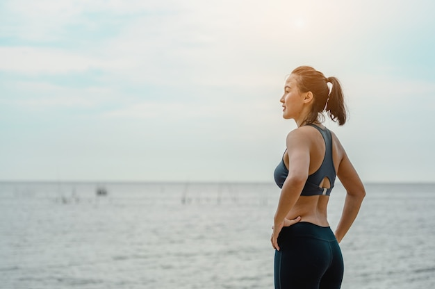 Aziatische vrouw staat om natuurlijke lucht in te ademen op het strand gezondfitness en lifestyle