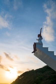 Aziatische vrouw steekt armen omhoog, zit bovenop een houten trap met avondrood op de achtergrond, overwinning, succesconcept
