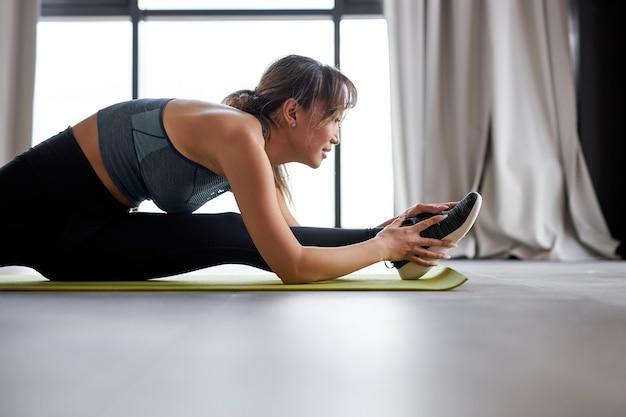 Aziatische vrouw strekt zich uit op de mat thuis, opleiding, benen strekken. training, recreatie, gezonde levensstijl concept