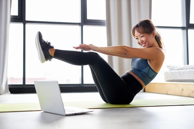 Aziatische vrouw thuis oefenen, kijken naar video-tutorial op laptop, training op de vloer. sport online concept