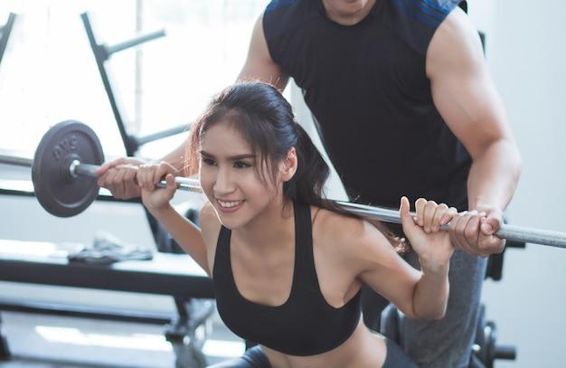 Aziatische vrouw tillen gewicht de rugligging persoonlijke trainer kan helpen