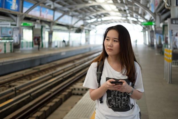 Aziatische vrouw toerist met behulp van smartphone tijdens reizen