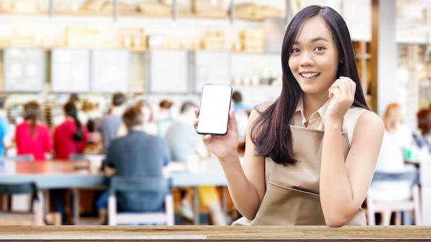 Aziatische vrouw toont leeg scherm op mobiele telefoon met café-achtergrond