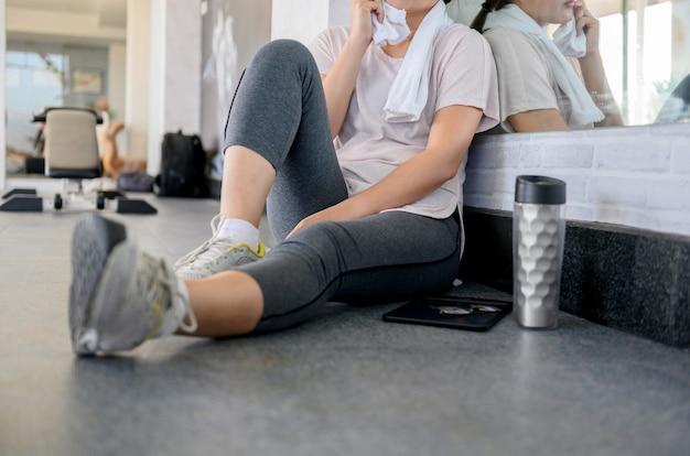 Aziatische vrouw traint en werkt alleen online bij gym. social distancing en nieuwe normale levensstijl.
